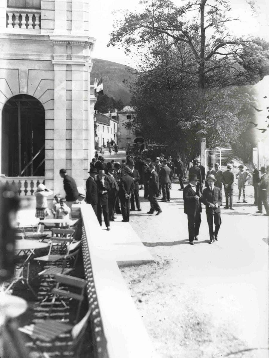 Photo d'archives de l'inauguration de l'Auberge des Dauphins en 1930 montrant une terrasse, le batiment et des personnes.