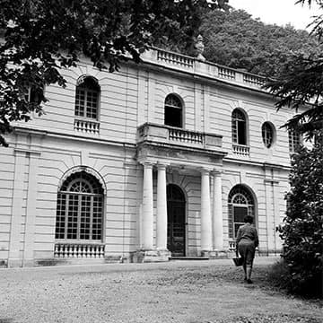 Photo d'archive de l'Auberge des Dauphins de 1960 montrant une des entrées de l'auberge entourée de colonnes.